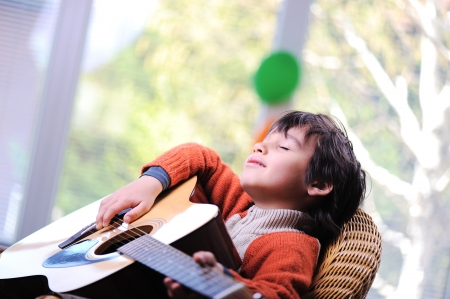 Kid playing guitar at home photo