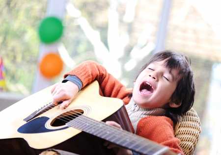 Kid singing and playing guitar at home photo