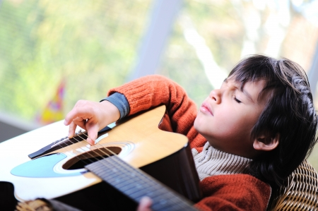 Little boy playing guitar at home photo