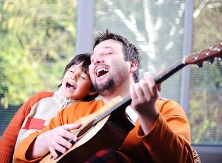 padre e hijo: Padre e hijo a tocar la guitarra en su casa Foto de archivo