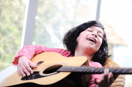 girl playing guitar: Little girl playing guitar at home