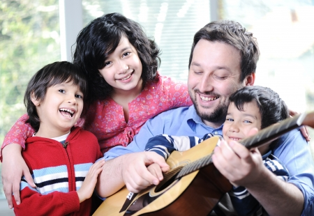 Happy family playing guitar together at home Stock Photo - 13665251