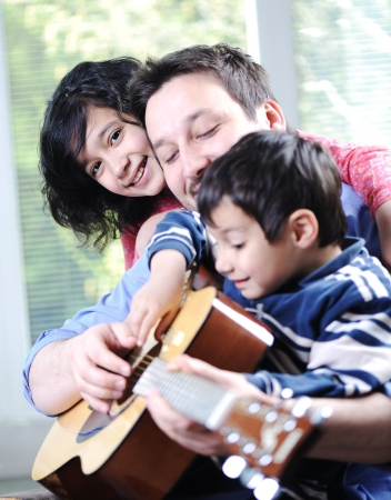 folk music: Happy family playing guitar together at home Stock Photo