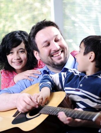 boy playing guitar: Happy family playing guitar together