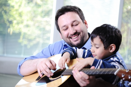 adult offspring: Father and son playing guitar at home Stock Photo