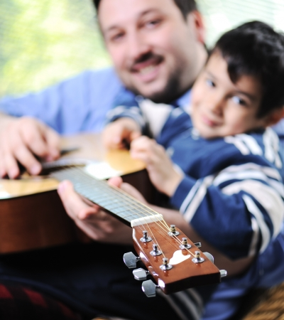 Father and son playing guitar at home Stock Photo - 13664981