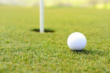 follow through: Golf ball at hole on grass field Stock Photo