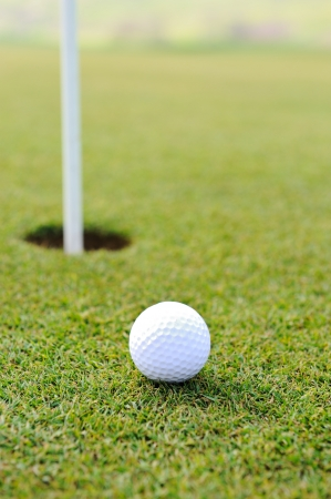 Ball and hole on golf field photo