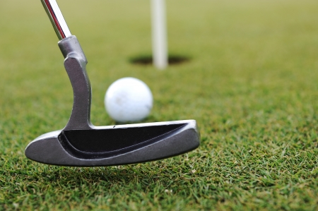 white hole: Golf Stick and Ball on the Green Grass Stock Photo