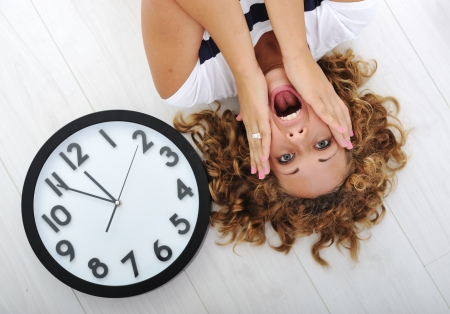 lay down: Girl and clock panic Stock Photo