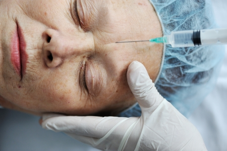 Senior woman getting on face injection at hospital photo