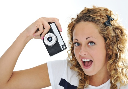 An excited young woman shouting holding a retro camera in hand  photo