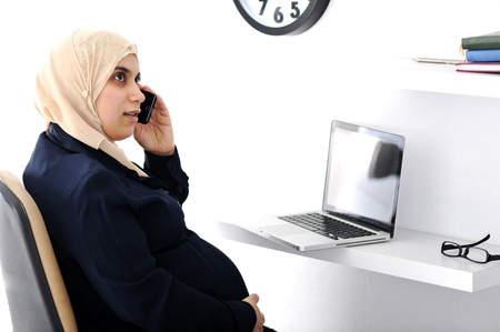 Pregnant Muslim Arabic business woman speaking on phone photo