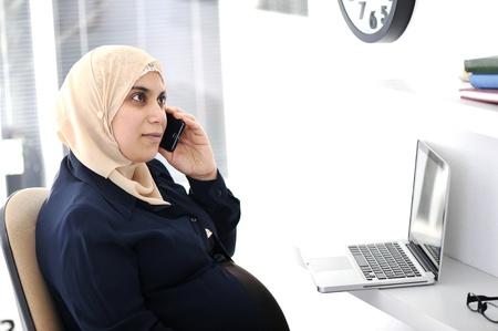 femmes muslim: Enceinte femme musulmane arabe entreprise travaillant au bureau