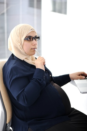 Pregnant Muslim Arabic business woman working at office photo
