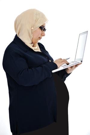 Pregnant Muslim Arabic woman using laptop photo