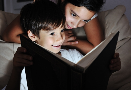 Boy and girl reading light book at night, children concept photo
