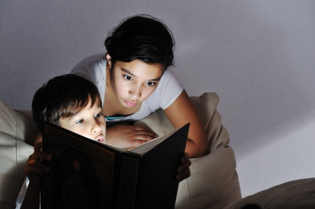 Brother and sister reading light book at night photo