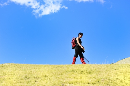 Hiker in mountains at grassland with sky above photo
