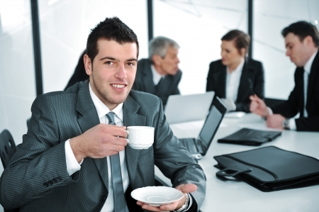 Businessman in business ambience drinking cofee photo