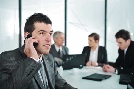 Business man speaking on the phone while in a meeting photo