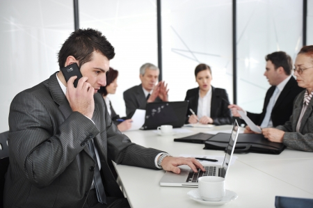 Business man speaking on the phone and typing on laptop while in a meeting photo