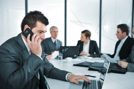 adviser: Business man speaking on the phone while in a meeting