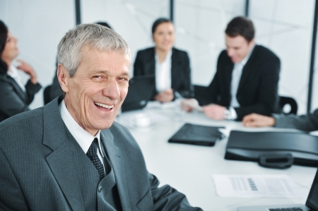 Senior businessman at a meeting laughing. Group of colleagues in the background photo