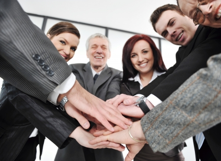 consensus: Group of executives placing their hands together