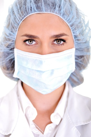 Female doctor wearing surgical cap and mask photo