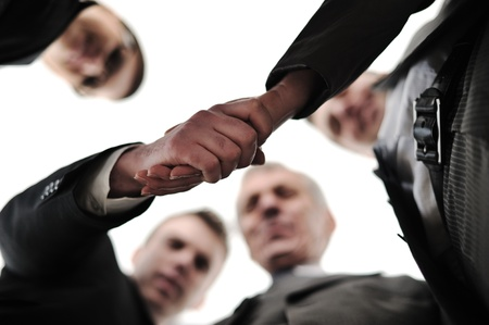 Two successful businessman shaking hands at front of corporate team in office photo