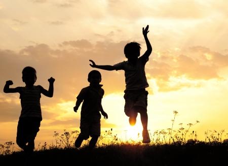 Children running on meadow at sunset photo