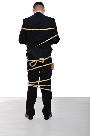 Businessman tied up on white background photo
