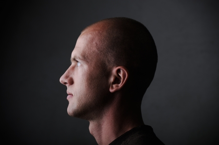 man face profile: Profile of white bald man in his twenties in dark Stock Photo