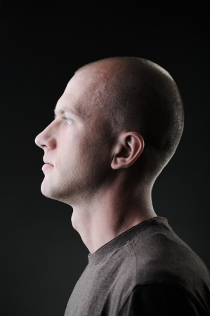 side pose: Profile of white bald man in his twenties in dark Stock Photo