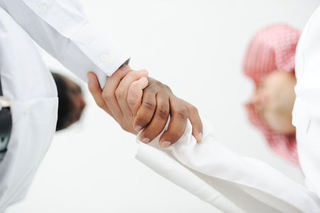 arab man: Closeup of business people shaking hands over a deal somewhere in the Middle east Stock Photo