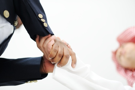 deal in: Closeup of business people shaking hands over a deal somewhere in the Middle east Stock Photo