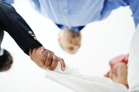 asian american: Closeup of business people shaking hands over a deal somewhere in the Middle east Stock Photo