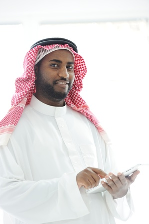 sheikh: Middle eastern man with gulf clothes using tablet at office Stock Photo
