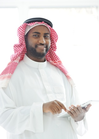 middle eastern clothes: Middle eastern man with gulf clothes using tablet at office Stock Photo