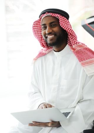 learning arabic: Black Arabic man working on laptop Stock Photo