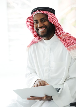 Black Arabic man working on laptop photo