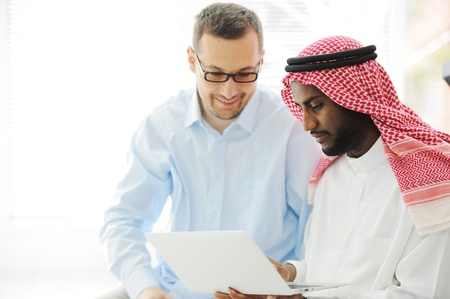 learning arabic: Arabic black and caucasian men working together on laptop Stock Photo
