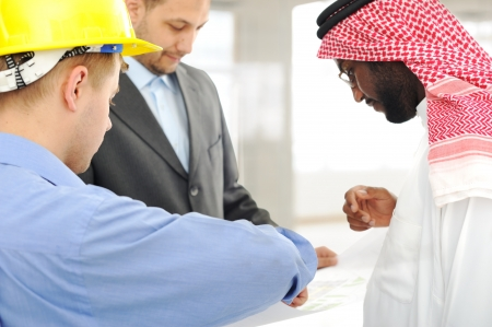 company building: Architects at Middle east discussing engineering design project