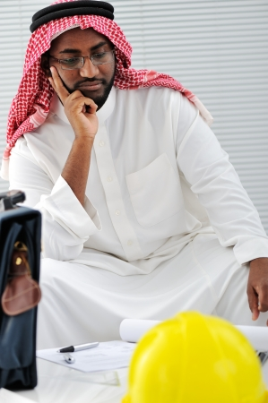Arabic engineer having a concern about the plans photo
