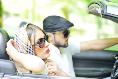 Two happy and sensual caucasian friends having drive on cabriolet car photo