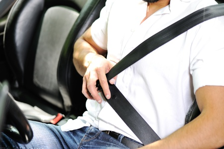 cinturon seguridad: El hombre la mano sujetar el cintur�n de seguridad en el coche Foto de archivo