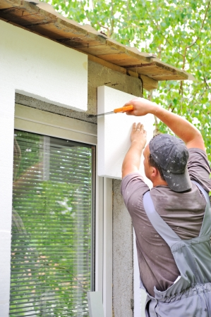 Construction worker applying insulation over exterior wall of house photo