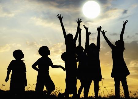 sol naciente: Los ni�os alza los brazos al sol en la pradera Foto de archivo