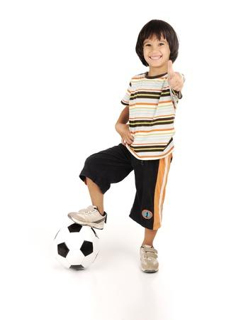 ni�o parado: Ni�o jugando f�tbol aisladas sobre fondo blanco Foto de archivo